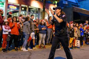 UW–Madison Police Chief Kristen Roman walks down State Street as thousands of spectators and children cheer during UW–Madison's Homecoming Parade.