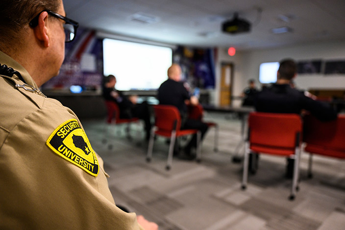 UW Police Department law-enforcement and security officers gather in a conference room for a debriefing.