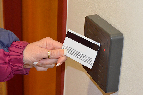 Person holding master key card up to a card reader.