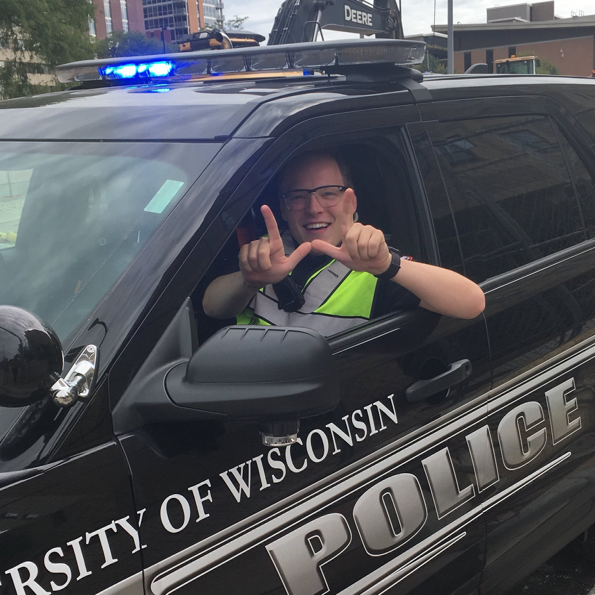 A photo of Officer Jake Lepper sitting in a police squad car and making a