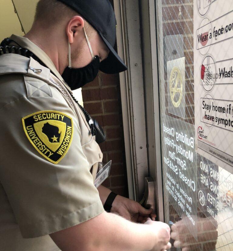 A security guard locks a building door.